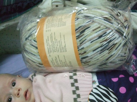Baby dwarfed by ball of yarn